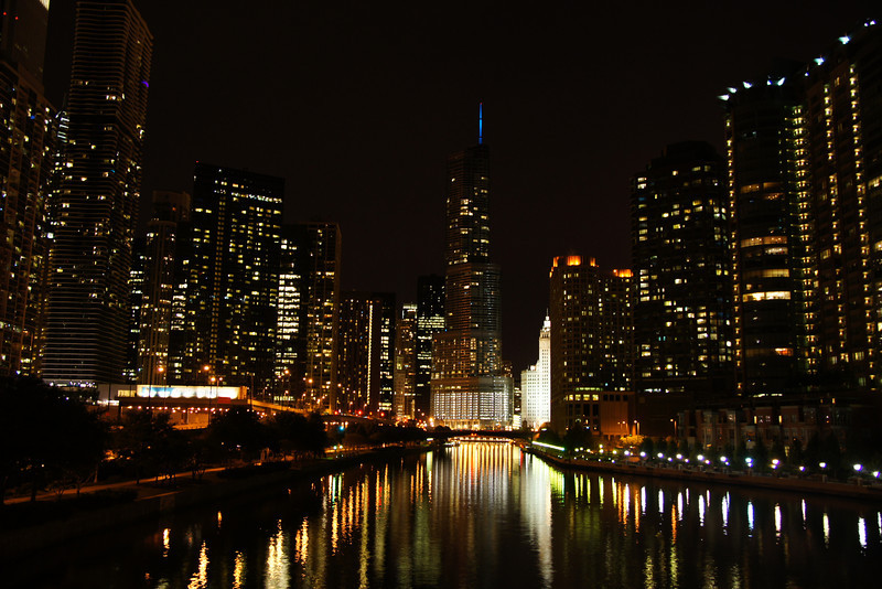 http://nomadicsamuel.com/destinations/chicago-at-night-photo-essay : A view of Chicago at night showcasing the large down town buildings and reflection in the water.